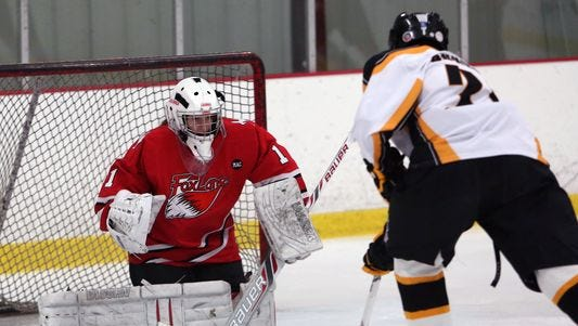 From left, Fox Lane goalie Abbie Ives (1) gets ready to stop a 3rd period shot from Lakeland/Panas' Colin Bonesso (31) during a hockey game at the Brewster Ice Arena Jan. 16, 2015. Fox Lane won the game 6-3.