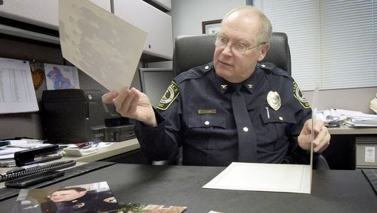 York Area Regional Police Chief Tom Gross looks over old photos of himself in December 2015, days before retiring. (Bill Kalina)