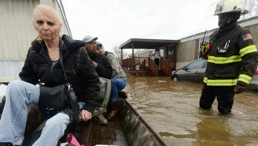 Marcie Traylor rides in a boat after being rescued from the Pecan Valley Mobile Home community that was flooded because of Wednesday rains. Bossier Firefighter Cameron LaCoure was out helping as well as neighbors who volunteered their boats for rescues.