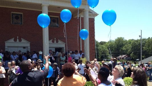 Balloons to honor victims of last summer's shooting at a church in Charleston are released following a prayer service last summer in Greer.