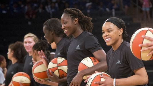 In this July 13, 2016 photo, members of the New York Liberty basketball team await the start of a game against Atlanta. The WNBA fined the Liberty, Phoenix Mercury and Indiana Fever and their players for wearing plain black warm-up shirts in the wake of recent shootings by and against police officers.