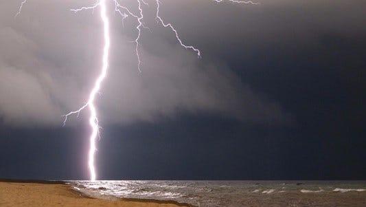 Lightning strikes near a beach.