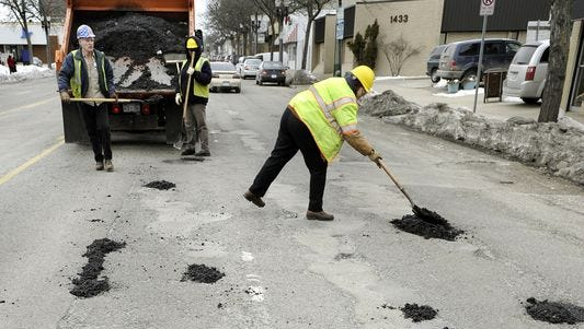 City of Lansing employees patch potholes on Michigan Avenue in 2011. The Lansing Regional Chamber of Commerce is asking the city to fix roads to accommodate all the new development along the corridor.