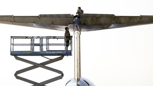 Two maintenance personnel work on the panel of a Allegiant Air MD-80 tail section at the McCarran International Airport in Las Vegas Tuesday, Oct. 25, 2016.