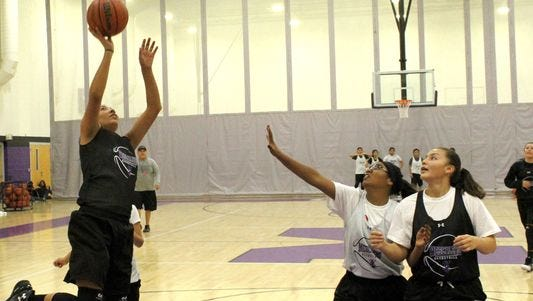 Katelyn Yuzos, left, puts up a layup during practice Thursday afternoon at the Mescalero Apache School gymnasium.
