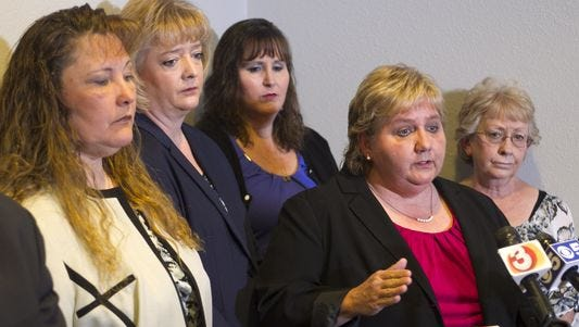Deb Harper speaks as (from left) Michelle Parker, Tracey Everitt, Jana Leineweber and Janet Sabol listen during a press conference at their attorney's office in Phoenix in 2014.