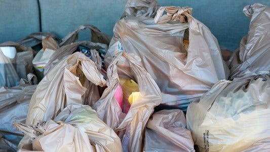 Plastic bags filled with groceries.