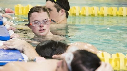 Aaron Coomes and his teammates rest in the pool during Waggener High School's swim practice at Northeast YMCA in Louisville.