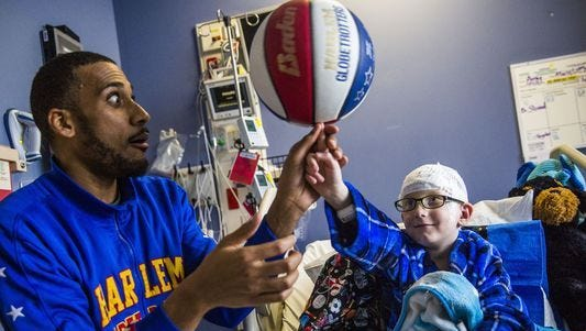 Harlem Globetrotters player Zeus McClurkin visits Jordon Simmons-Zalewski, 7, of Fort Myers, in his hospital room at Golisano Children's Hospital of Southwest Florida in Fort Myers.