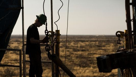 A worker prepares to hoist a joint of drill-stem pipe on a rig working in the Permian Basin.