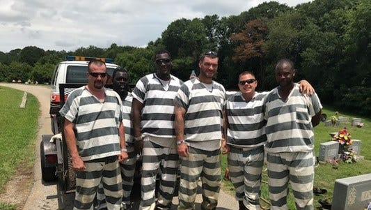 Six inmates are being praised after they helped save an officer who passed out during a work detail by calling 911.