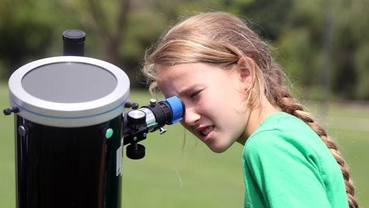 Gillian Hester looks at the sun through a solar telescope during an eclipse party on Aug. 21, 2016, in Nashville.