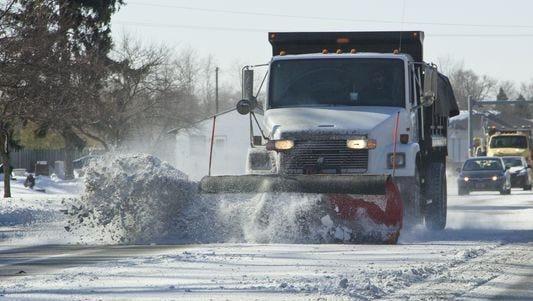 A truck plows snow.