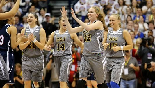 Lauren Hill, a freshman battling an inoperable rare form of brain cancer, celebrates with her Mount St. Joseph basketball teammates after making the first basket of the game against Hiram College at Xavier University's Cintas Center.