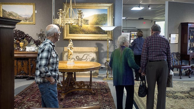Guests stroll through shelves of displays with everything from paintings to jewelry bidding March 18, 2016 at Brunk Auction. Guests can wander through the facility to browse at items while auctioning is going on.