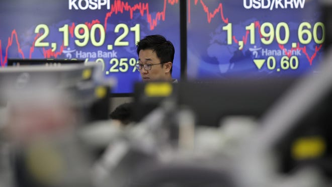 A currency trader walks by the screens showing the Korea Composite Stock Price Index (KOSPI), left, and the foreign exchange rate between U.S. dollar and South Korean won at the foreign exchange dealing room in Seoul, South Korea, Thursday, June 11, 2020.