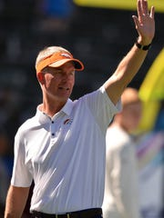 Denver Broncos offensive coordinator Mike McCoy waves before the game against the Los Angeles Chargers at StubHub Center.