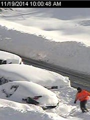 In this photo from a surveillance camera operated by the New York State Thruway Authority, a person climbs through piles of snow next to abandoned vehicles on the Thruway, near Lackawanna, N.Y., Wednesday, Nov. 19, 2014. A 132-mile stretch of the state Thruway in western New York remains closed as authorities continue their efforts to rescue motorists stranded on a Buffalo-area section of the highway.