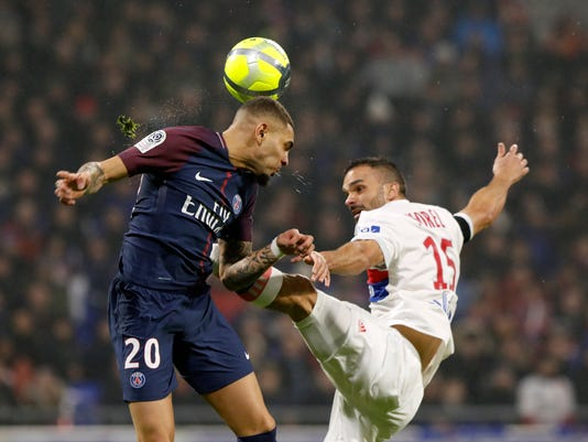 PSG's Layvin Kurzawa, left, challenges for the ball with Lyon's Jeremy Morel, right, during the French League One soccer match between Lyon and Paris Saint Germain in Decines, near Lyon, central France, Sunday, Jan. 21, 2018. (AP Photo/Laurent Cipriani)