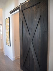 A wooden barn door is used to separate the den from