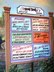 Old advertising signs grace a canvas backdrop on the