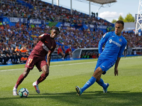 "FILE - In this Sept. 16, 2017 file photo, Barcelona's Ousmane Dembele, left, duels with Getafe's Juan Torres Ruiz ""Cala"" before getting injured during a Spanish La Liga soccer match between Getafe and Barcelona at the Alfonso Perez stadium in Getafe, outside Madrid. Spanish league teams are seldom happy when playing at Getafe's small stadium in southern Madrid, no matter the result of their matches. Win or lose, teams have been complaining of poor field conditions at the Coliseum Alfonso Perez, which has been attracting more attention than the hosts' decent Spanish league campaign so far. Barcelona had already complained of the stadium's field, saying it helped cause Ousmane Dembele's injury. (AP Photo/Francisco Seco, File)"