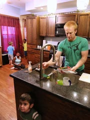 Gregg Eichhorn, 30, gets breakfast ready for his eight children he and his wife, Katie, 29, have adopted (one is pending). Seven have special needs. The couple met as teenagers and married when they were 19 and 18. Eichhorn starts his dad with prayer, before getting medicines ready, kids dressed and breakfast on the table.
