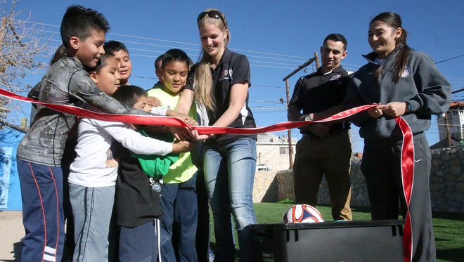 Kiersten Gerrand, center, and other students from the UTEP Doctor of Physical Therapy program help children cut the ribbon on a new backyard soccer field at La Posada Home at 1020 N. Campbell Monday. About 33 students from the program's Class of 2016 raised more than $6,500 to purchase and install the synthetic turf at the shelter.