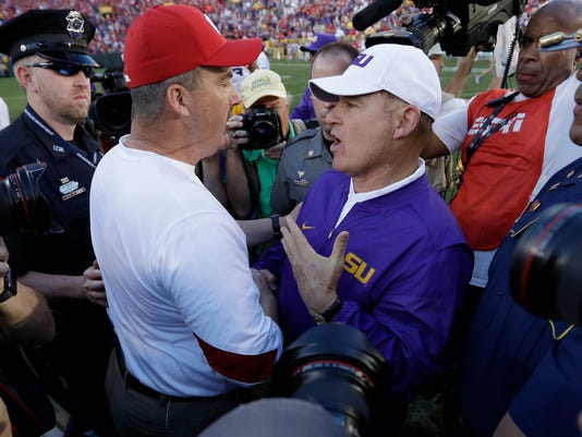 FILE - In this Saturday, Sept. 3, 2016, file photo, LSU head coach Les Miles talks to Wisconsin head coach Paul Chryst after Wisconsin won 16-14 in an NCAA college football game in Green Bay, Wis. In recent years, voters have become more comfortable making dramatic shifts in early season polls ,  which is how you get LSU dropping 16 spots after one loss and Wisconsin going from unranked to 10th. (AP Photo/Morry Gash, File)