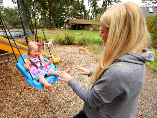 Ellie Stafford, 2, laughs while swinging with her mother