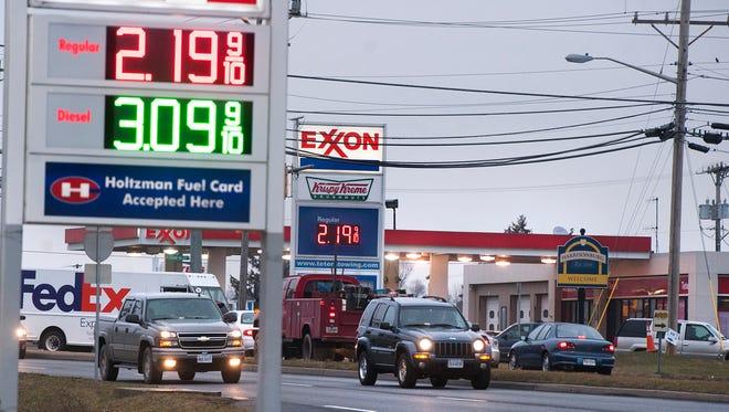 Motorist drive past signs advertising gas prices in Harrisonburg, Va.,