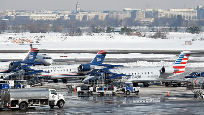 Planes sit among snow at Washington's Ronald Reagan National Airport on Monday, Jan. 25, 2016.