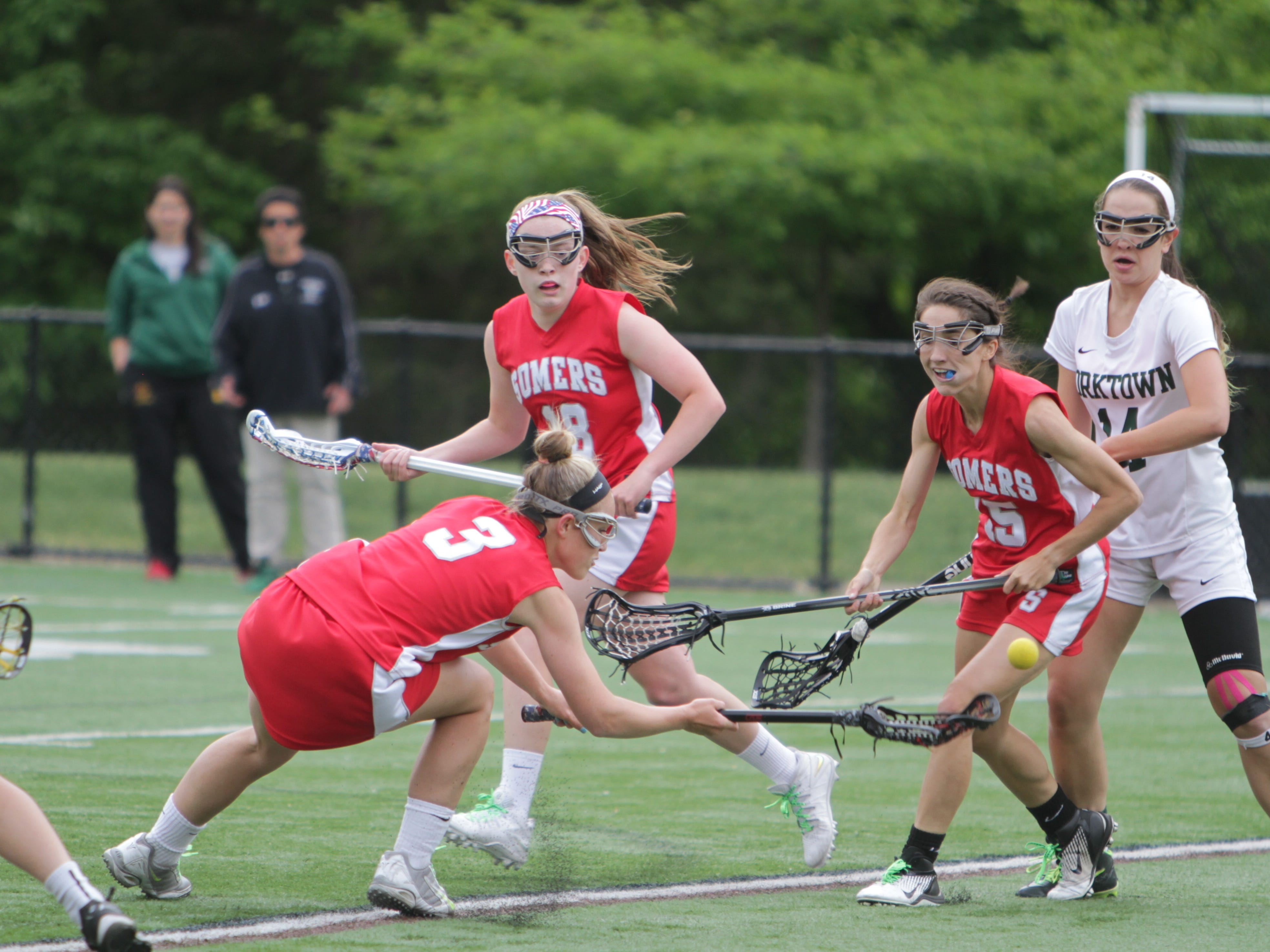 Somers' Gabby Rosenzweig goes for a ground ball, with teammates Christine Olert (18) and Sydney Ericson (15) looking on during the Class B final at Torne Valley Stadium. Somers won 10-9.