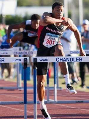 Isaiah Oliver of Brophy Prep takes the lead  in the boys 110 high hurdles at the Chandler Rotary Track Invitational on Saturday March 21, 2015 in Chandler.