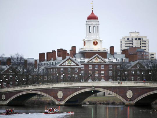 In this March 7, 2017, file photo, rowers paddle along the Charles River past the Harvard College campus in Cambridge, Mass. A 2018 lawsuit alleging bias at Harvard's admissions office is pulling back the curtain on the secretive, complex process that decides who gets a place at one of the world's most selective institutions.