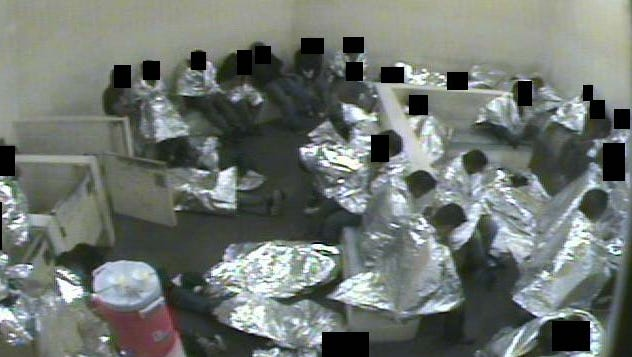 Men, wrapped in Mylar sheets, sit and lie in a concrete cell in this Aug. 2015 video still from the U.S. Border Patrol Tucson detention facility.