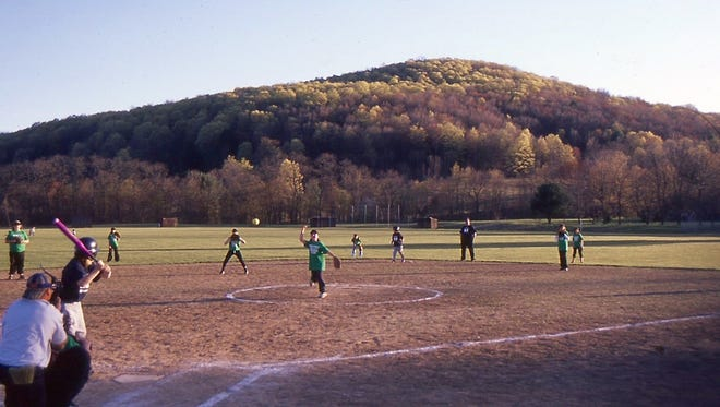 A softball game provided a view of a forested hill covered with yellow-green maple trees.