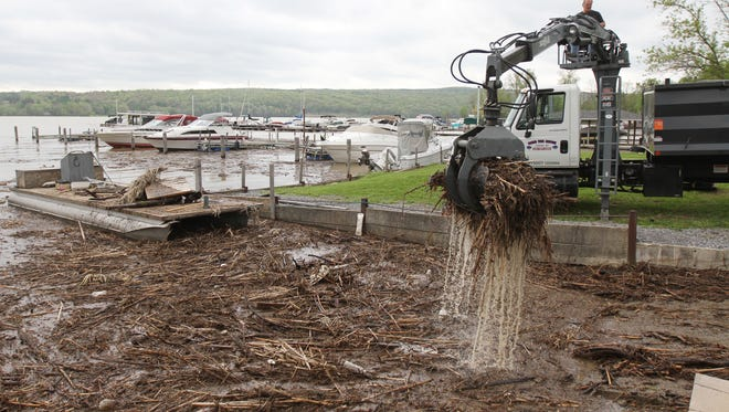 File Photo: Steve Renco, of Renco 's Tree Service, and also a friend of Nancy and George Sproule help them remove trees and other debris they were trying to clean up at their marina on Keuka Lake.  The couple owns Harbor Club Marina in Branchport.
