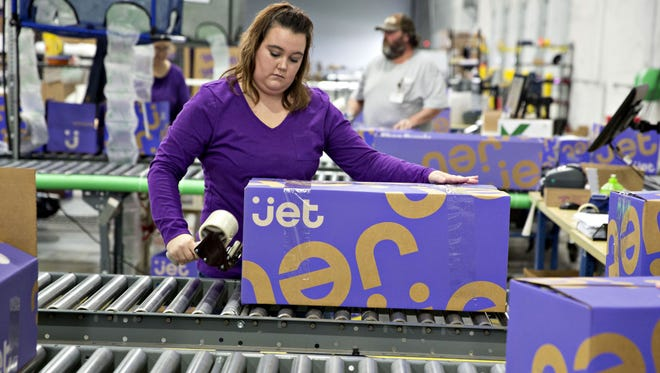 """An employee tapes a box shut at the Jet.com Inc. fulfillment center on Cyber Monday in Kansas City, Kan. Jet says the """"holiday gift rush"""" has strained its fulfillment centers and the company can no longer guarantee delivery by Christmas on some items."""