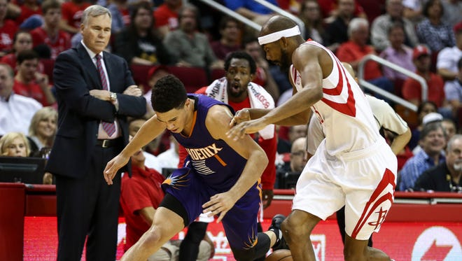 Phoenix Suns guard Devin Booker (1) loses control of the ball as Houston Rockets forward Corey Brewer (33) defends during the first quarter at Toyota Center.