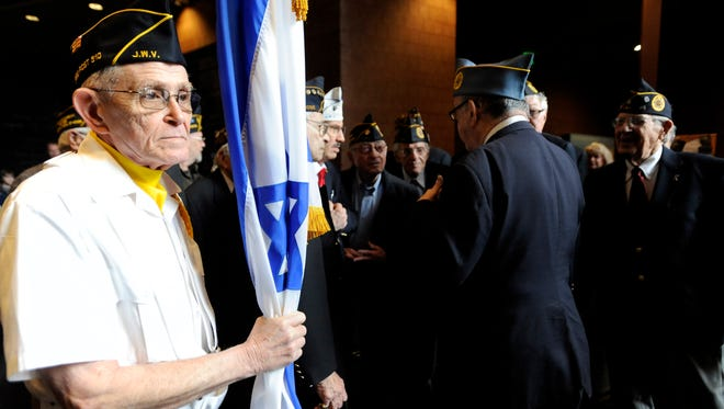 Marv Delidow, a Jewish War Veteran for the U.S. Army, waits to carry in the Israeli flag for the posting of the colors during Yom HaShoah, a Holocaust Day of Remembrance, at the Holocaust Memorial Center in Farmington Hills, Mich., on Sunday, April 7, 2013. (AP Photo/Detroit News, Elizabeth Conley)