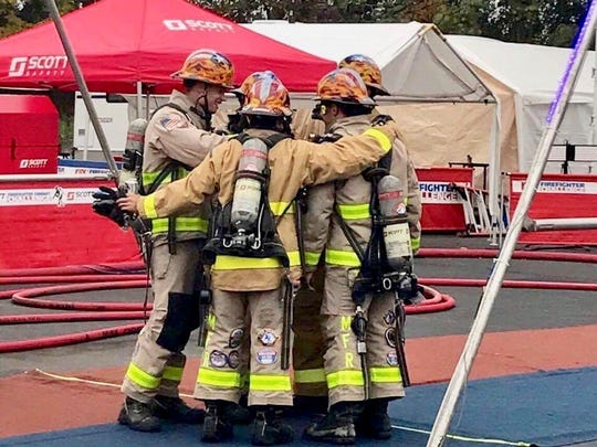 The Montgomery Fire/Rescue Blue Team poses under their combat challenge race time. The team beat out the Slovakian national team to bring home the world championship title.