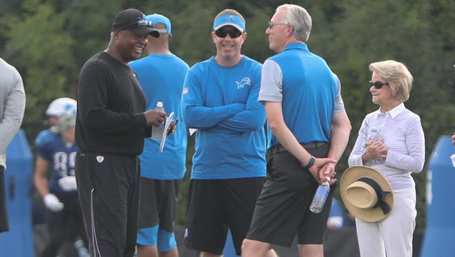 From left, coach Jim Caldwell chats with GM Bob Quinn, president Rod Wood and owner Martha Ford.