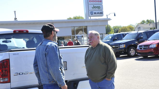 Doug Johnson, co-owner of Johnson & Sons Co., right, talks to customer Bill Yaun of Wisconsin Rapids, outside the family-owned dealership.