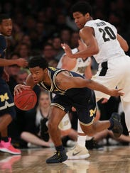 Michigan guard Zavier Simpson steals the ball from Purdue guard Nojel Eastern during the Big Ten title game March 4, 2018 at Madison Square Garden in New York.