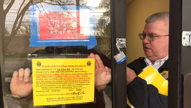 East Lansing fire marshal Gerald Rodabaugh posts a notice Wednesday with the reasons why the Abbot Manor building can't be occupied.