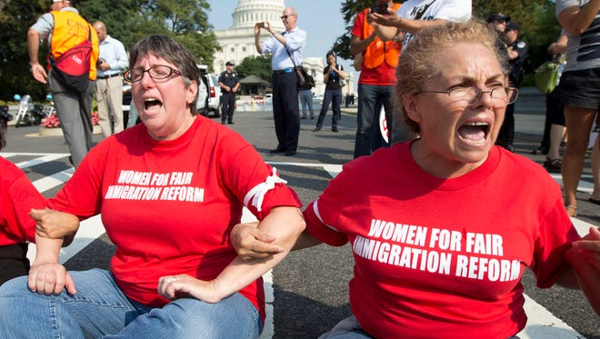 Women link arms and sit in a circle to block the intersection of Independence Avenue Southeast and New Jersey Avenue Southeast outside the House of Representatives in Washington on Sept. 12  during a protest of Congress' inaction on a comprehensive immigration overhaul.