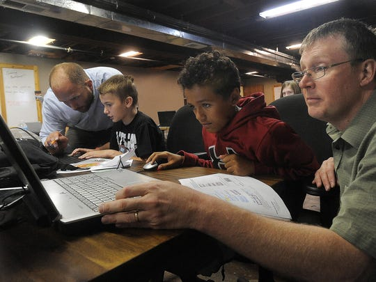 Insturctors Brad Hartzler (left) and Will Bushee (right) guide students Aiden Worshek (second from left), 10, and Ray Suttle, 11, during Code Bootcamp of South Dakota's five-day gaming bootcamp Thursday in the basement of the Rock Island Building in Sioux Falls.