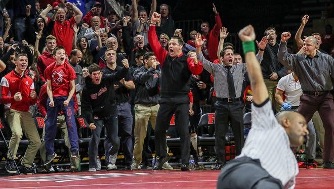 Rutgers coach Scott Goodale, center, and fans celebrate a rare pin against Michigan.