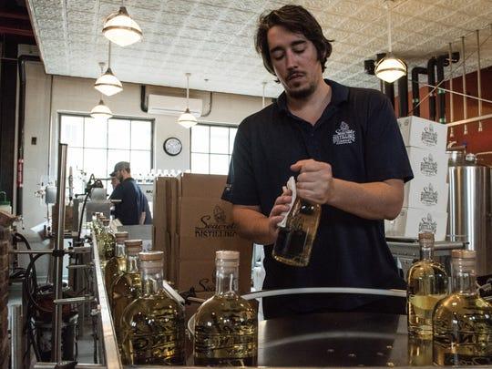 Matt Albright packages bottles of Seacrets' rum on